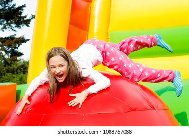 Happy little girl having lots of fun on a inflate castle while jumping.