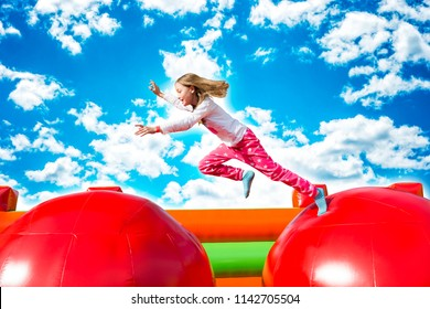 Happy little girl having lots of fun while jumping from ball to ball on an inflate castle.