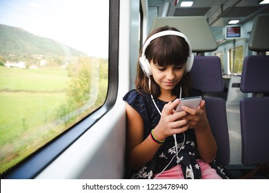 Happy little girl with headphones using her smart phone while travelling by train