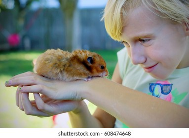 Happy little girl with her cute pet hamster