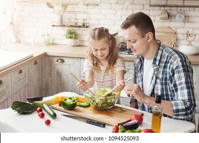 Happy little girl and her dad cooking at home kitchen. Father and daughter making vegetable salad and having fun together. Fathers day, family and healthy food concept