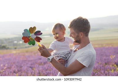 Happy little girl and her father on lavender background. Cute baby playing in meadow field. Family holiday in summer day.