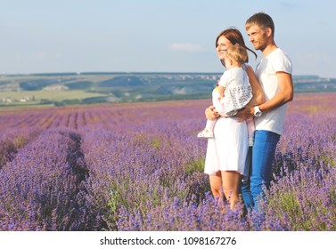 Happy little girl and her mother, father on lavender background. Cute baby playing in meadow field. Family holiday in summer day.