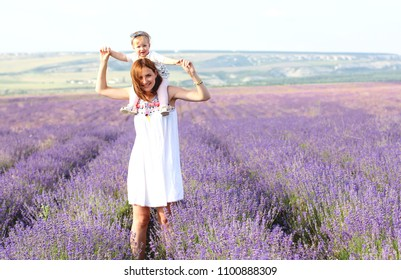 Happy little girl and her mother on lavender background. Cute baby playing in meadow field. Family holiday in summer day.