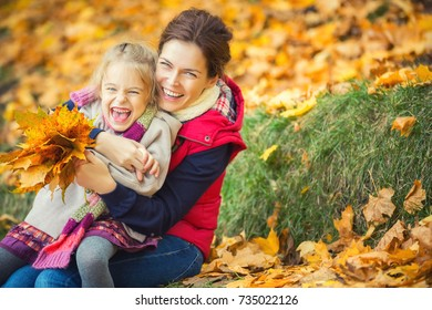 Happy little girl and her mother enjoy walk in autumn park and play with bright autumn leaves