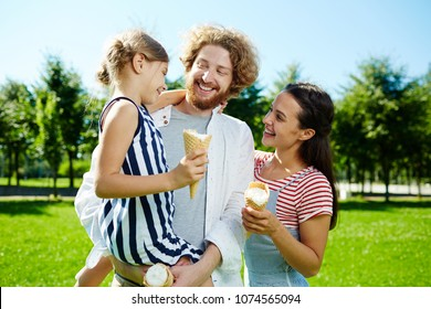 Happy little girl and her parents with icecreams talking and enjoying sunny day in park