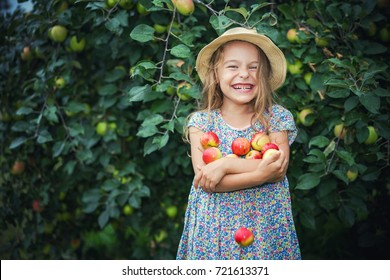 Happy little girl holding apples in the garden