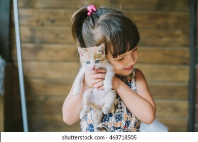 happy little girl holding a cat in her arms