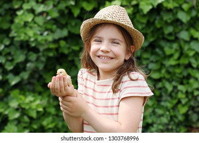 Happy little girl is holding a chicken