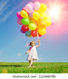 Happy little girl holding colorful balloons. Child playing on a green meadow. Smiling 