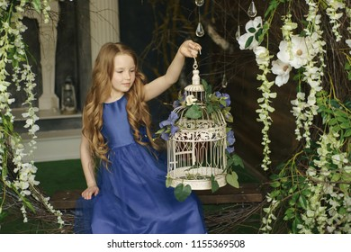 happy little girl holding decorative bird cage full of flowers. Studio shot in provence style interior