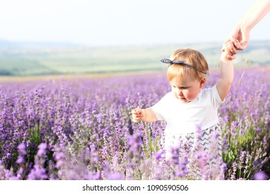 Happy little girl holding a hand of her mother on lavender background. Cute baby playing in meadow field. Family holiday in summer day.