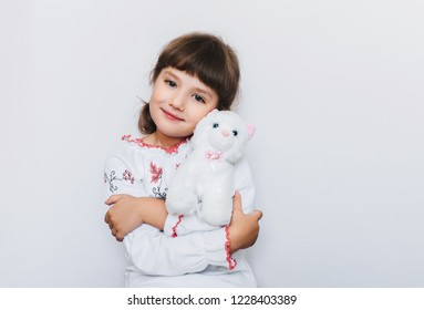 Happy little girl hugging her favorite white kitten soft toy. Favorite toys of children. Orphanage. Copy space.