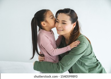 Happy little girl hugging and kissing her mother in living room at home , family and happy people concept