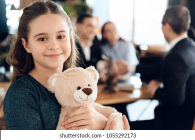 Happy little girl is hugging teddy bear at office of family lawyer. Registration of guardianship. Family in office of family lawyer.