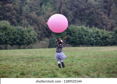 Happy little girl with an inflatable pink ball running on a green field in the park