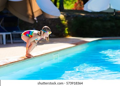Happy little girl with inflatable toy ring jumping into outdoor swimming pool in a tropical resort during family summer vacation. Kids learning to swim. Water fun for children
