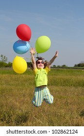 happy little girl jumping with balloons on meadow