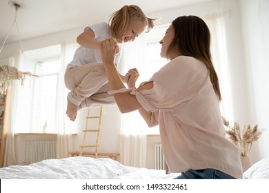 Happy little girl jumping in bed holds mom hands view from bottom, fit family funny leisure activity at home daughter and mother priceless time together in morning after night or daytime sleep concept