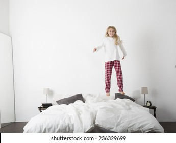 Happy Little Girl Jumping in bed with a smile on her face