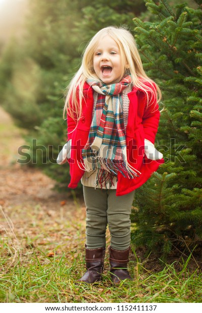 Happy little girl jumping in fur tree farm. Playful time. Happiness concept.