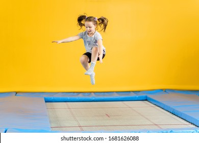 Happy little girl jumping on trampoline in fitness center