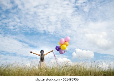 Happy little girl jumping on green meadow holding colorful air balloons