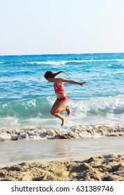 Happy Little Girl Jumping In Sea Waves. Jump Accompanied By Water Splashes. Summer Sunny Day, Ocean Coast