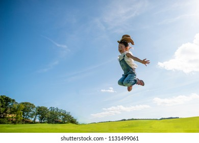 Happy Little Girl Jumping To The Sky