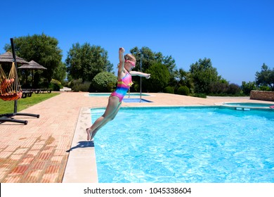 Happy little girl jumping in the swimming pool. Cute kid enjoying summer vacation in beautiful villa or resort. Luxury summer vacation for family with children.