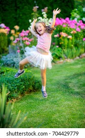 happy little girl jumps on a lawn near flowers, it is a lot of emotions
