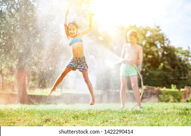 Happy little girl jumps under water, when brother pours her from garden hose. Hot summer days activity.