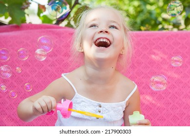 Happy little girl laugh with soap bubbles on a pink background