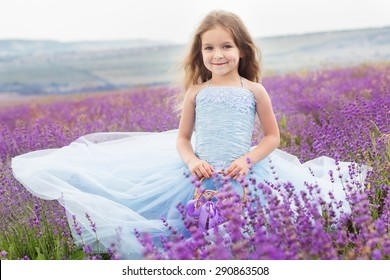 Happy little girl is in a lavender field holds a basket with ribbon