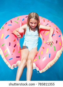 Happy little girl laying on a colorful inflatable donut with a drink in a  swimming pool.
