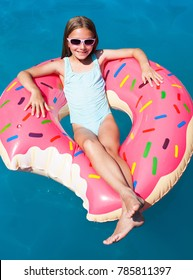 Happy little girl laying on a colorful inflatable donut in a  swimming pool.