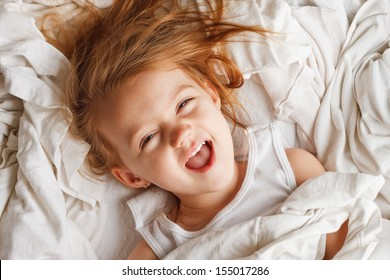 Happy little girl laying in white laundry