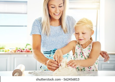 Happy little girl learning to make dough and pastry as she helps her mother in the kitchen with the baking, with copy space