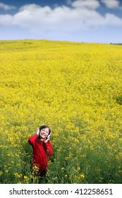 happy little girl listening music on field