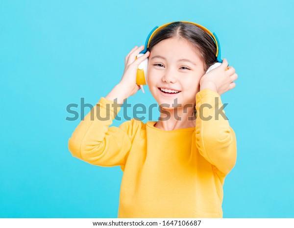 Happy little girl   listens to music in headphones