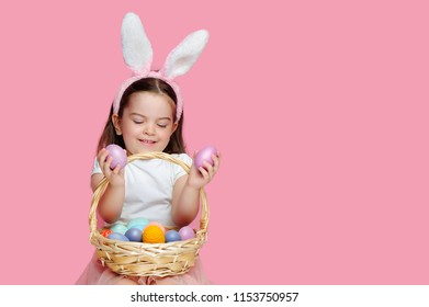 Happy little girl looking at pink Easter eggs in her hands