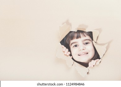 Happy little girl looking through a paper hole