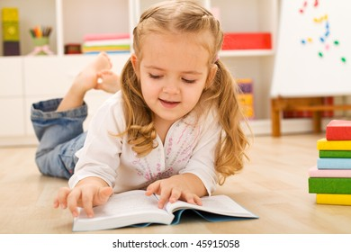 Happy little girl with lots of books laying on the floor at home