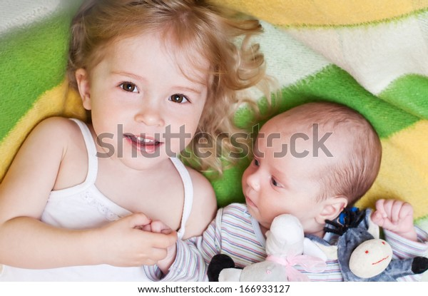happy little girl lovingly holding the hand of a newborn brother in bright blanket