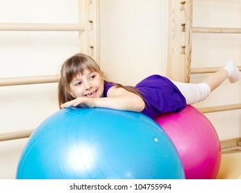Happy little girl lying on large gymnastic balls