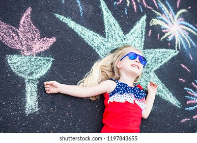 Happy little girl lying on asphalt with painted torch. Cute Caucasian girl wearing stars and stripes dress and sunglasses. Independence day