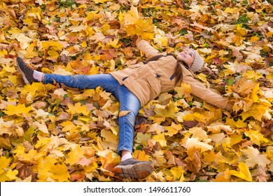 Happy little girl lying on the fallen leaves arms outstretched and holding the bouquets of yellow maple leaves in her hands