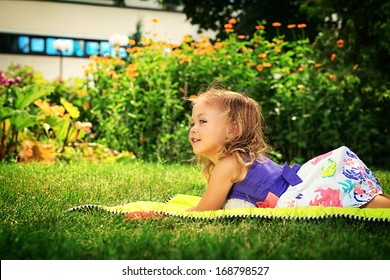 Happy little girl lying on a grass at the park.