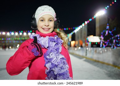 Happy little girl makes excellent gesture on the silent disco skating in the winter evening