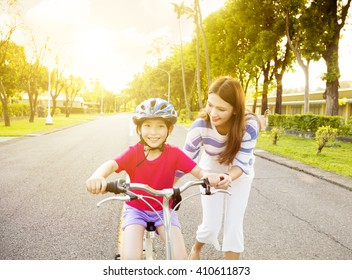 happy little girl with mother practice to riding  bicycle